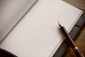 ペンで手帳にメモする