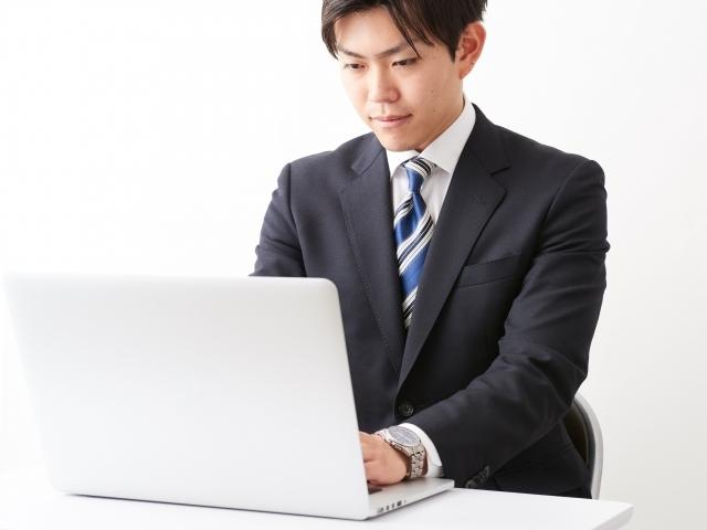 スーツとネクタイ着用でパソコンに向かうビジネスマン