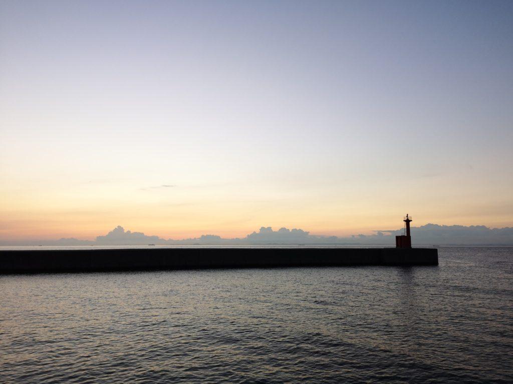夏の夕暮れと堤防と灯台と雲
