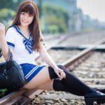 アジアの女子高生と通学カバンと線路