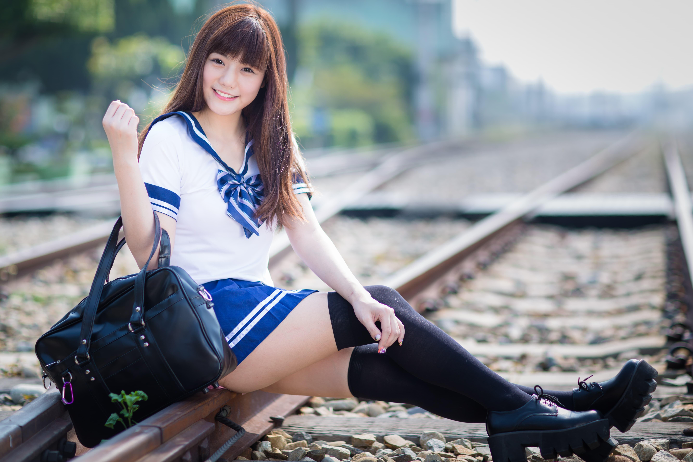 アジアの女子高生と通学カバンと線路(人)