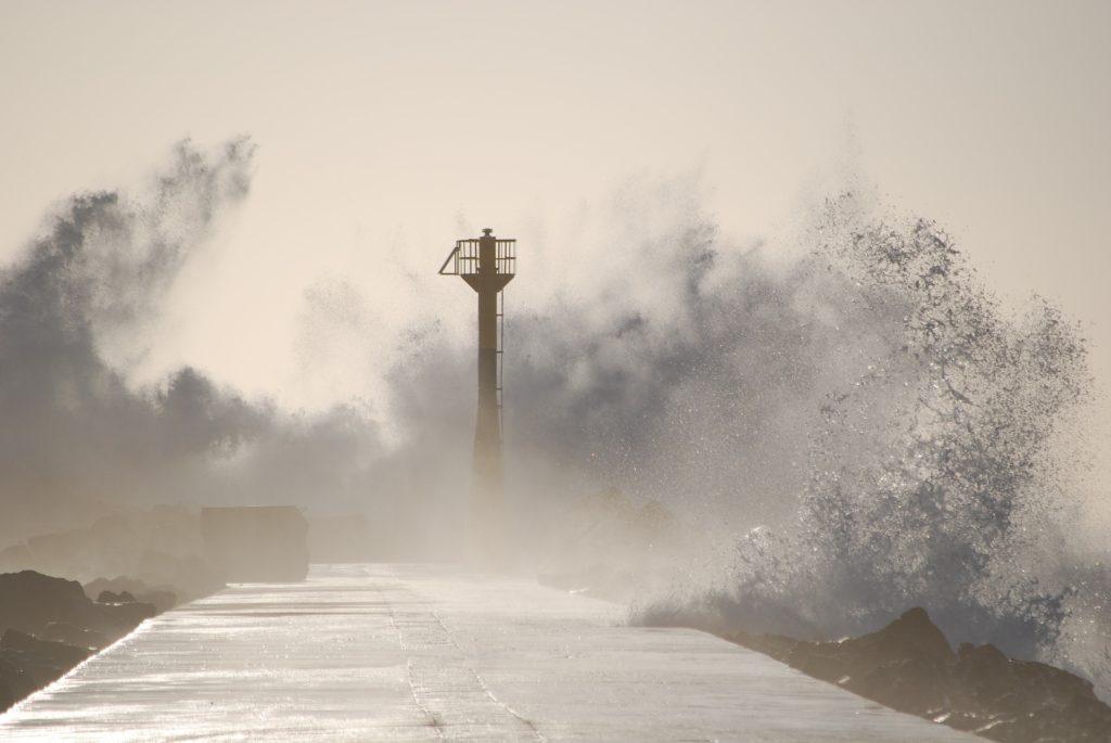 大荒れの堤防と灯台と越波と台風と