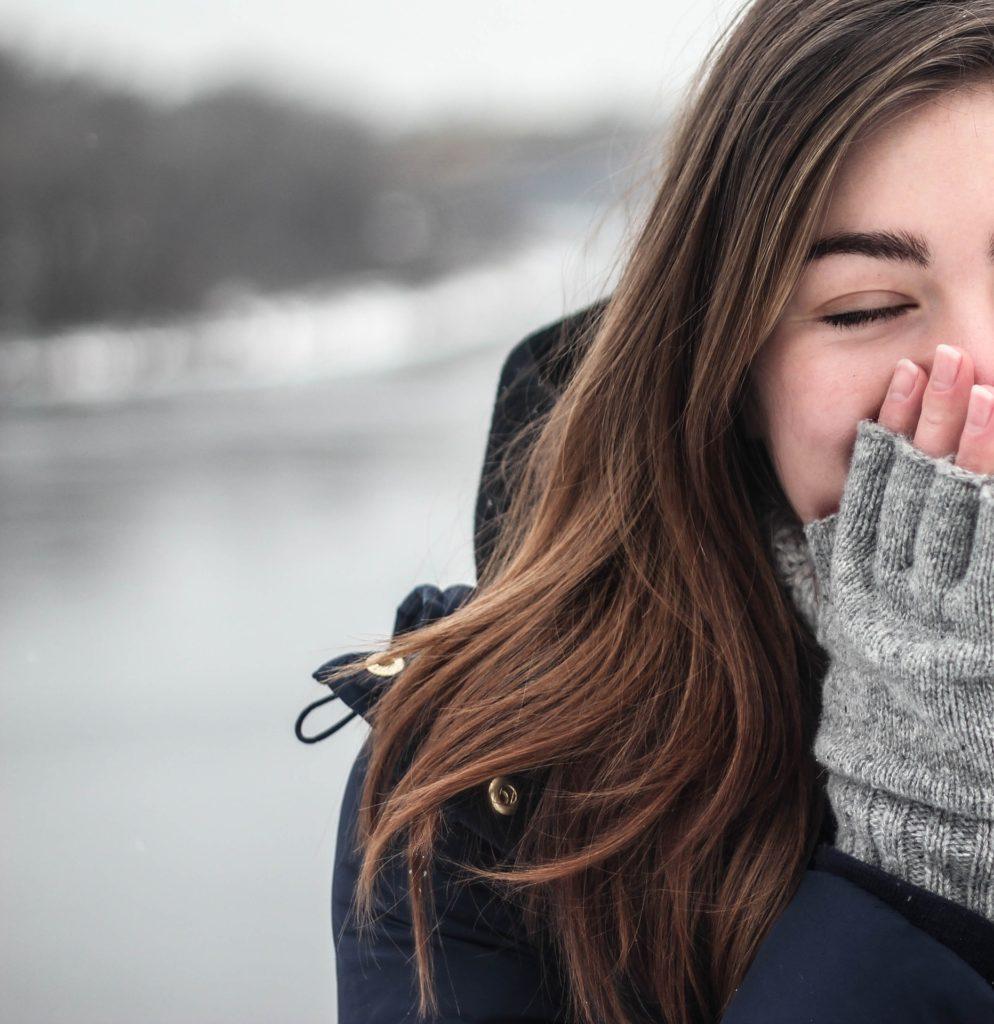 手袋をして息を吐く女性の喜びと寒さ