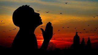 日の出の協会で祈りを捧げ考える男