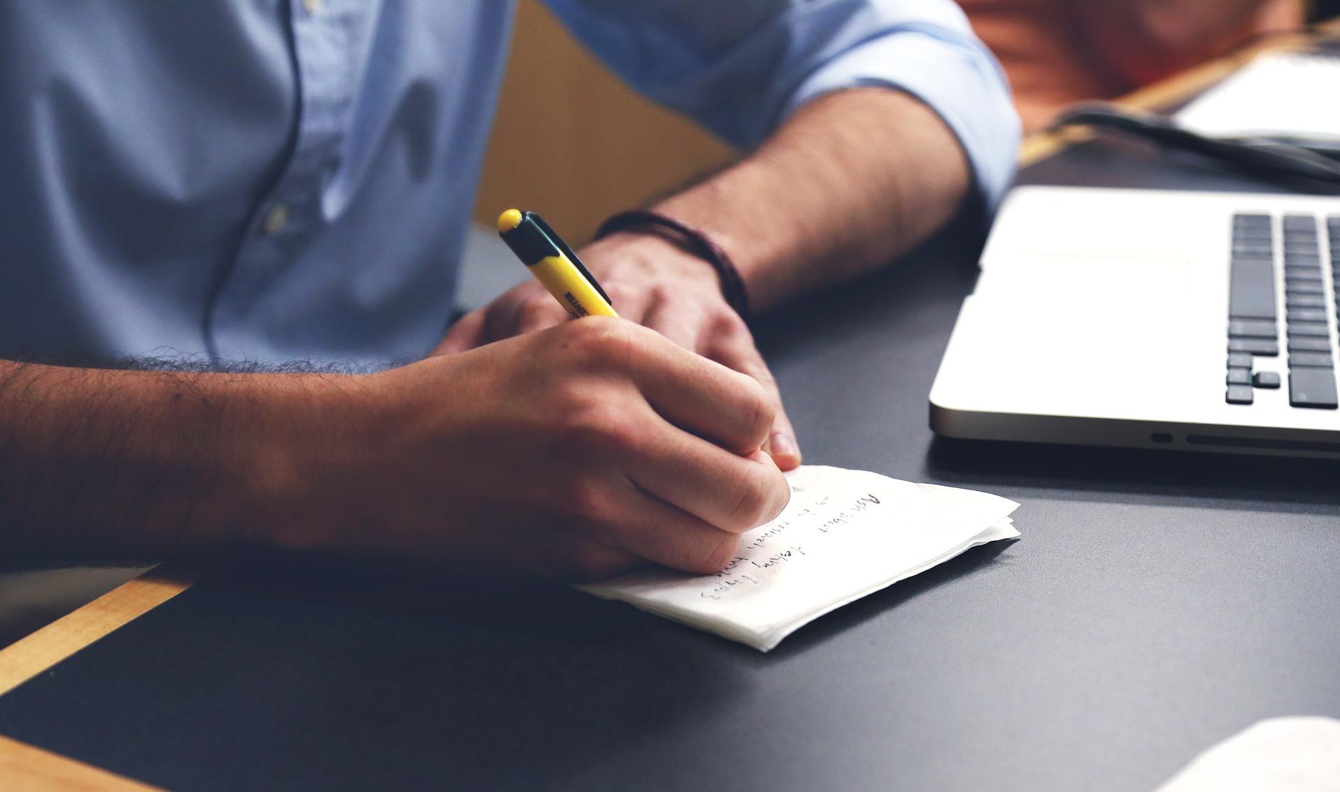 パソコンとメモと手帳に計画目標を書く人