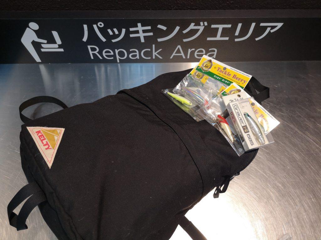 釣り具ルアーとデイパックと羽田空港のパッキングエリア