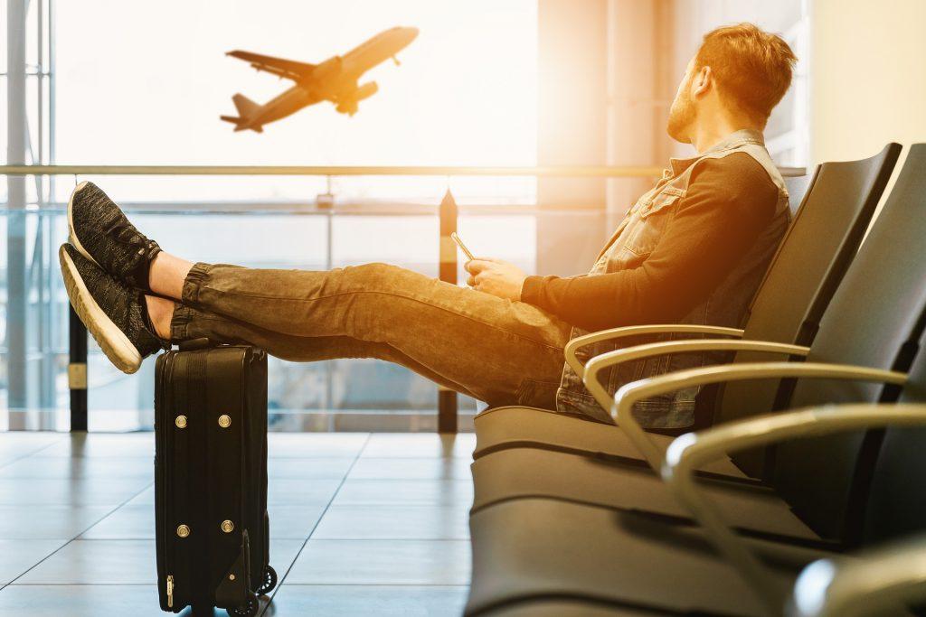 空港でスマホ片手に飛行機をみながら時間を潰す男性の手荷物(人)