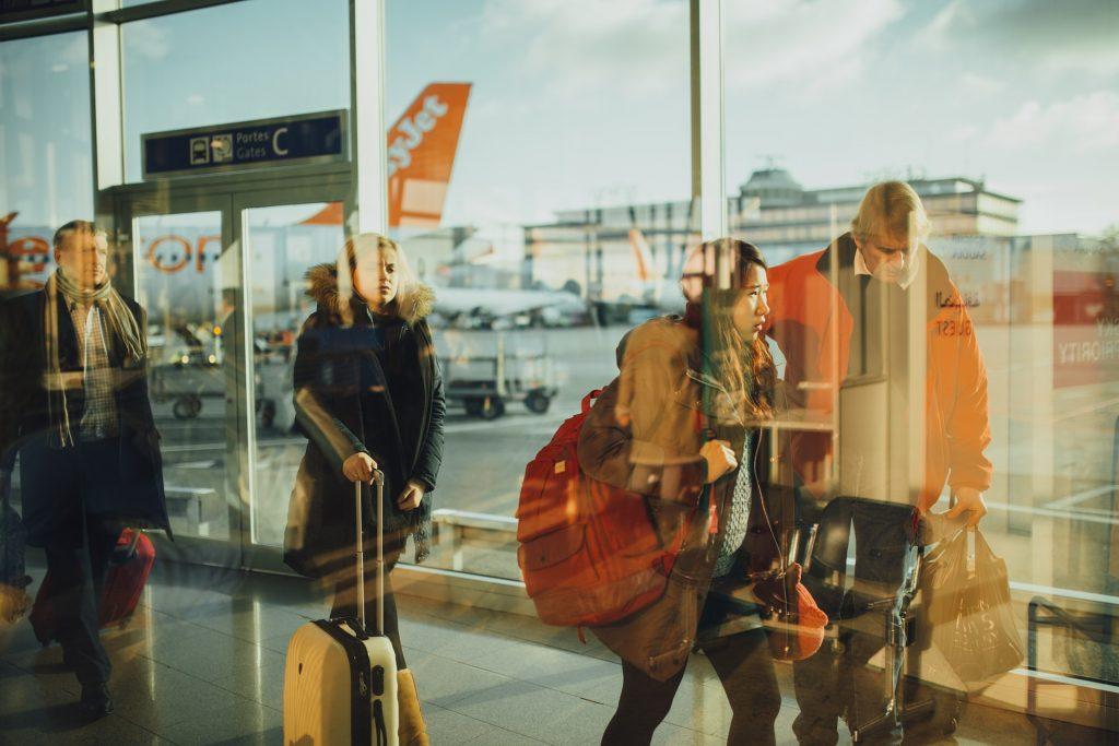空港で飛行機から降りてきた(乗る?)荷物を抱えた人たち