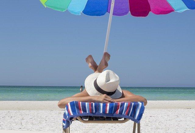 ビーチパラソルの下でパナマ帽子を被ってくつろぐビーチリゾート
